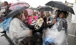 Ladies' Day at Aintree Races, Liverpool, 13 Apr 2012 Ladies' Day at Aintree races, and a fine example of Britain's practical approach to bad weather. Photograph: McPix Ltd/Rex Features