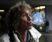 55-year-old homeless Honza B. smokes a used cigarette butt as he escorts his tour group in Prague